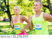 Купить «happy couple of sportsmen racing wit badge numbers», фото № 32278910, снято 16 августа 2015 г. (c) Syda Productions / Фотобанк Лори