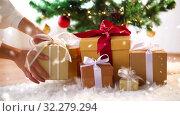 Купить «hands taking gift box from under christmas tree», видеоролик № 32279294, снято 16 ноября 2019 г. (c) Syda Productions / Фотобанк Лори