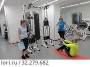 Купить «Инструктор рассказывает, как правильно выполнять упражнение», эксклюзивное фото № 32279682, снято 7 февраля 2018 г. (c) ДеН / Фотобанк Лори