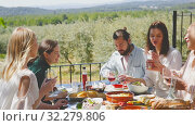 Купить «Friends dinner al fresco. Group of happy adult people sitting together at table outdoors in country house, eating are smiling», видеоролик № 32279806, снято 26 апреля 2019 г. (c) Яков Филимонов / Фотобанк Лори