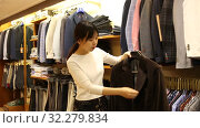 Купить «Polite young Chinese salesgirl offering stylish suit coats in men clothing store», видеоролик № 32279834, снято 6 июня 2019 г. (c) Яков Филимонов / Фотобанк Лори