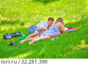 Купить «Russia, Samara, May 2019: a girl and a young student give lectures while lying on the grass in a park on a summer sunny day.», фото № 32281390, снято 1 июня 2019 г. (c) Акиньшин Владимир / Фотобанк Лори