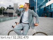 Businessman with bike drinks coffee in downtown. Стоковое фото, фотограф Tryapitsyn Sergiy / Фотобанк Лори