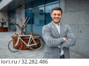 Smiling businessman with bicycle at glass building. Стоковое фото, фотограф Tryapitsyn Sergiy / Фотобанк Лори