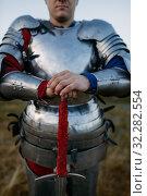 Купить «Medieval knight in metal armor holds sword», фото № 32282554, снято 5 июля 2019 г. (c) Tryapitsyn Sergiy / Фотобанк Лори