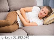 Купить «Girl is lying unhappy because she has a stomach ache», фото № 32283070, снято 4 октября 2017 г. (c) Яков Филимонов / Фотобанк Лори
