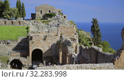 Купить «Mass tourism in the ancient Greek amphitheater, Taormina, Ionian Sea view», видеоролик № 32283998, снято 17 мая 2019 г. (c) Ирина Мойсеева / Фотобанк Лори