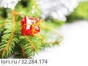 Купить «Little gift box in red with a gold ribbon on the branches of a Christmas or New Year tree, on a white background», фото № 32284174, снято 10 октября 2019 г. (c) Юлия Бабкина / Фотобанк Лори