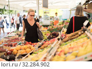 Woman buying fruits and vegetables at local food market. Market stall with variety of organic vegetable. Стоковое фото, фотограф Matej Kastelic / Фотобанк Лори