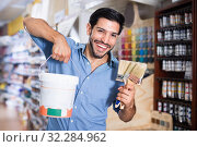 Man standing amongst racks in paint store with brushes and paint. Стоковое фото, фотограф Яков Филимонов / Фотобанк Лори