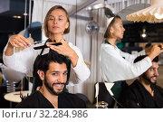 Купить «hairdresser working with scissors and comb», фото № 32284986, снято 22 октября 2019 г. (c) Яков Филимонов / Фотобанк Лори