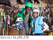 Купить «Cheerful African American man and his preteen son posing in full skiing gear during shopping in sport goods store», фото № 32285278, снято 16 апреля 2019 г. (c) Яков Филимонов / Фотобанк Лори