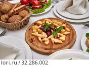 Купить «Small pieces of cheese of different varieties lie on a wooden plate on a served table in restaurant», фото № 32286002, снято 23 августа 2019 г. (c) Олег Белов / Фотобанк Лори