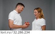 Купить «happy man giving little red present to woman», видеоролик № 32286234, снято 10 октября 2019 г. (c) Syda Productions / Фотобанк Лори