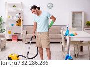 Купить «Young injured man cleaning the house», фото № 32286286, снято 29 июля 2019 г. (c) Elnur / Фотобанк Лори
