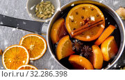 Купить «pot with hot mulled wine, orange slices and spices», видеоролик № 32286398, снято 24 мая 2020 г. (c) Syda Productions / Фотобанк Лори