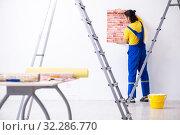 Купить «Young man contractor doing renovation at home», фото № 32286770, снято 4 июня 2019 г. (c) Elnur / Фотобанк Лори
