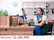 Купить «Young handsome contractor cleaning the office», фото № 32286986, снято 9 мая 2019 г. (c) Elnur / Фотобанк Лори