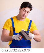 Купить «Young contractor employee applying plaster on wall», фото № 32287970, снято 15 марта 2018 г. (c) Elnur / Фотобанк Лори