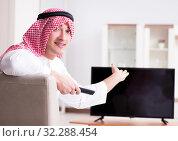Купить «Arab man watching tv at home», фото № 32288454, снято 12 марта 2018 г. (c) Elnur / Фотобанк Лори