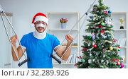 Купить «Injured man celebrating christmas at home», фото № 32289926, снято 26 июля 2017 г. (c) Elnur / Фотобанк Лори