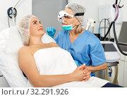 Купить «Professional cosmetician examining face skin of girl in clinic of esthetic cosmetology», фото № 32291926, снято 14 марта 2019 г. (c) Яков Филимонов / Фотобанк Лори