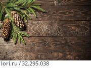 Купить «fir branches and cone on dark old wooden background», фото № 32295038, снято 13 октября 2019 г. (c) Майя Крученкова / Фотобанк Лори
