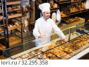 Купить «Male baker is offering fresh tasty bun», фото № 32295358, снято 26 января 2017 г. (c) Яков Филимонов / Фотобанк Лори