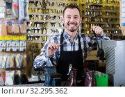 Worker demonstrating newly shaped key. Стоковое фото, фотограф Яков Филимонов / Фотобанк Лори