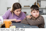 Upset boy and angry mother having quarrel during breakfast at home. Стоковое фото, фотограф Яков Филимонов / Фотобанк Лори