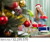 Smiling girl in Santa hat with Xmas presents. Стоковое фото, фотограф Яков Филимонов / Фотобанк Лори