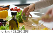 Купить «woman adding lettuce to salad bowl at home kitchen», видеоролик № 32296298, снято 10 октября 2019 г. (c) Syda Productions / Фотобанк Лори