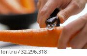 Купить «hands peeling carrot with vegetable peeler», видеоролик № 32296318, снято 10 октября 2019 г. (c) Syda Productions / Фотобанк Лори