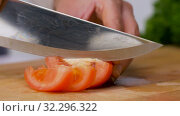 woman chopping tomato with kitchen knife at home. Стоковое видео, видеограф Syda Productions / Фотобанк Лори