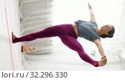 Купить «woman doing yoga hand-to-big-toe pose at studio», видеоролик № 32296330, снято 9 октября 2019 г. (c) Syda Productions / Фотобанк Лори