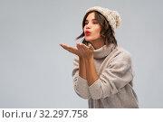 Купить «young woman in knitted winter hat sending air kiss», фото № 32297758, снято 30 сентября 2019 г. (c) Syda Productions / Фотобанк Лори