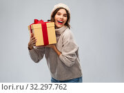 Купить «young woman in knitted winter hat holding gift box», фото № 32297762, снято 30 сентября 2019 г. (c) Syda Productions / Фотобанк Лори