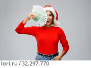 Купить «happy woman in santa hat with money on christmas», фото № 32297770, снято 30 сентября 2019 г. (c) Syda Productions / Фотобанк Лори