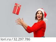 Купить «happy young woman in santa hat catching gift box», фото № 32297786, снято 30 сентября 2019 г. (c) Syda Productions / Фотобанк Лори