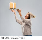 Купить «young woman in winter hat catching gift box», фото № 32297934, снято 30 сентября 2019 г. (c) Syda Productions / Фотобанк Лори