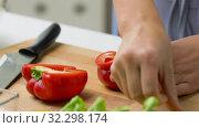 Купить «woman cutting pepper in half and removing seeds», видеоролик № 32298174, снято 10 октября 2019 г. (c) Syda Productions / Фотобанк Лори