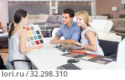 Young family consulting with seler about sofa color. Стоковое фото, фотограф Яков Филимонов / Фотобанк Лори