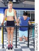 Couple exercising push-ups on bars. Стоковое фото, фотограф Яков Филимонов / Фотобанк Лори
