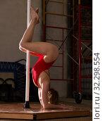 Attractive sports girl in red swimsuit dancer engaged on pylon. Стоковое фото, фотограф Яков Филимонов / Фотобанк Лори