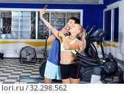 Купить «Smiling athletic pair making selfie during break in workout session at gym», фото № 32298562, снято 16 июля 2018 г. (c) Яков Филимонов / Фотобанк Лори