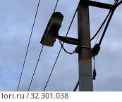Уличная камера видеонаблюдения пристегнута цепью закреплена на столбе. Стоковое фото, фотограф Кузнецов Максим / Фотобанк Лори