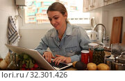 Portrait of enthusiastic young woman sitting with laptop at home kitchen. Стоковое видео, видеограф Яков Филимонов / Фотобанк Лори