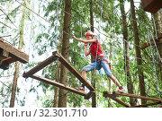 Купить «Girl at climbing activity in high wire forest park», фото № 32301710, снято 1 июля 2017 г. (c) Дмитрий Калиновский / Фотобанк Лори