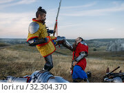 Купить «Medieval knight in armor prepares to cut off head», фото № 32304370, снято 5 июля 2019 г. (c) Tryapitsyn Sergiy / Фотобанк Лори