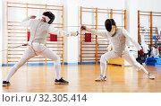 Купить «Portrait of athletes at fencing workout, practicing attack movements in duel», фото № 32305414, снято 11 июля 2018 г. (c) Яков Филимонов / Фотобанк Лори